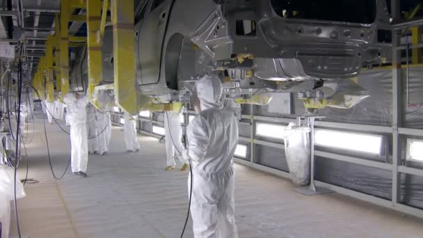 workers are painting car bodies by airbrushes, they are wearing protective overalls