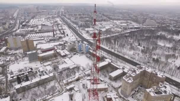 aerial view on modern telecommunication tower, buildings and roads of modern industrial city in winter