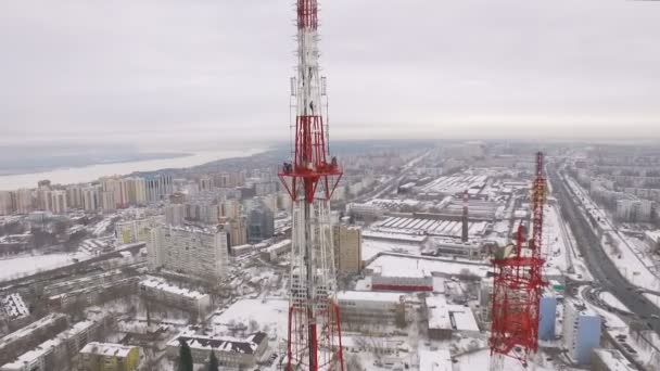 aerial camera is flying along site with workers on hight on tv tower
