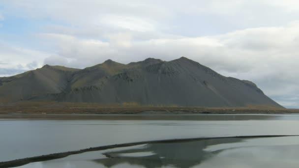 klid a dramatický islandských krajina s temnými horami a široká řeka v oblačné počasí