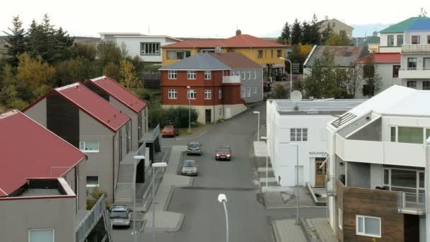 kis Izlandi utcai házak, autó parkolt őszi nap, egy piros autó mozgásban