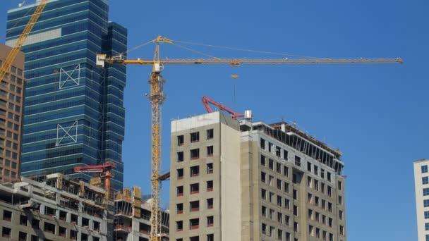 Zobrazit na stavební jeřáb a nedokončené budově v moderním městě v letním dni