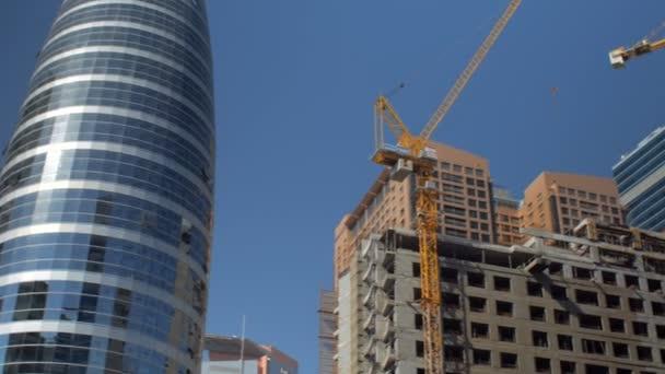 Panorama topy nedokončené stavby budov s jeřáby v letním dni