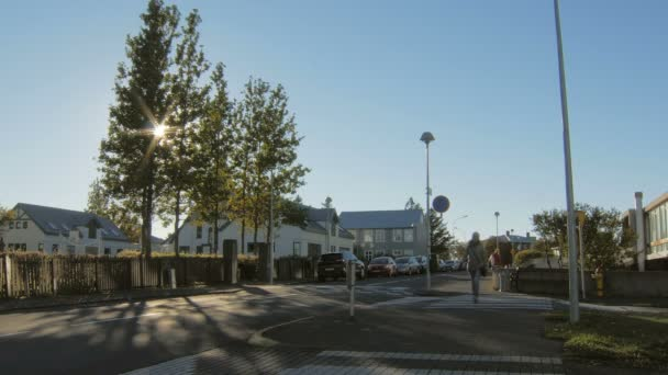 blonde woman is crossing a pedestrian passages in suburban area in sunny autumn day