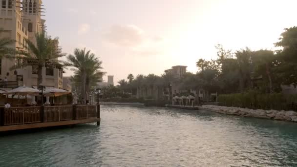 landscape with canal, tropical palms and traditional arabic buildings with cafe in evening