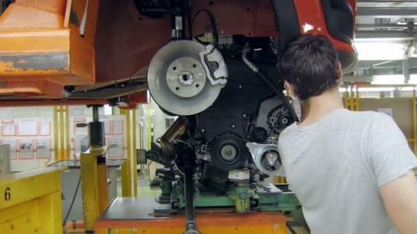 instalace motoru v autě na automobilový závod, pracovník používá automatický Hydraulický zvedák