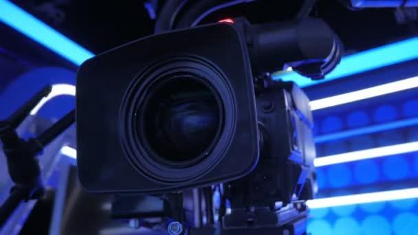 Nahaufnahme einer Fernsehkamera auf einem Kran, die sich in einem dunklen Studio bewegt, beleuchtete Dekoration