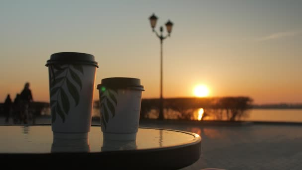 two cardboard cups with coffee are standing in a table of quay cafe in sunset, silhouette of people