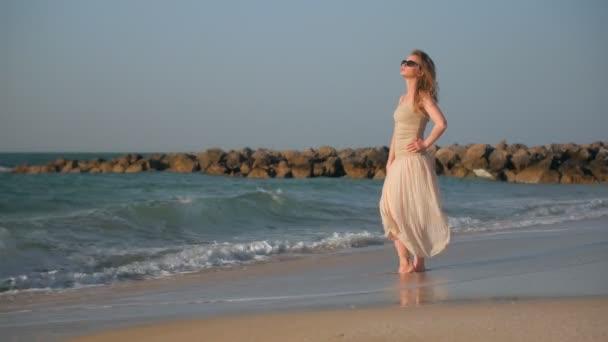 csinos nő állt a tengerpart, a nyári nap, a hullámok mosás lábát, látszó-on vasárnap