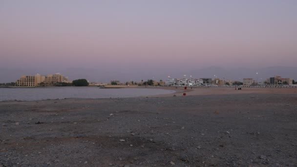 city beach and small bay of sea in a twilight, huge mountains are in background in a night mist