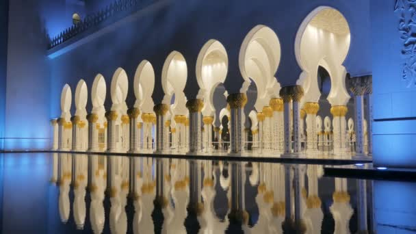 ABU DHABI, U.A.E. - JAN, 2018: Sheikh Zayed Grand Mosque, gallery with walking people and reflection in a fountain in night time