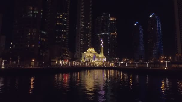 night view on beautiful small mosque in Dubai Marina, view from floating pleasure boat