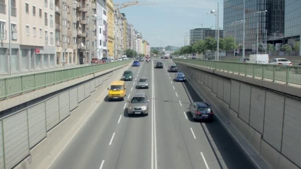 automobilové dopravy ve městě v slunečný den, vozidla se pohybují do tunelu, pohled z mostu