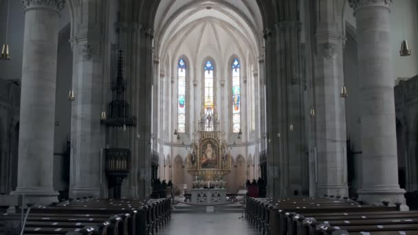inside praying hall of catholic cathedral with grey columns and stained glasses