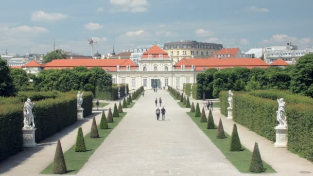 people are walking in Baroque park landscape of Belvedere in sunny summer day, cut green bushes