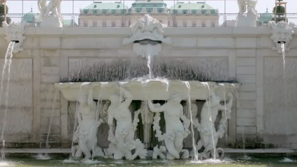 sculptures of naked people in white baroque fountain in palace garden