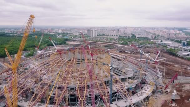 camera is flying over large sportive arena under construction with city panorama in background