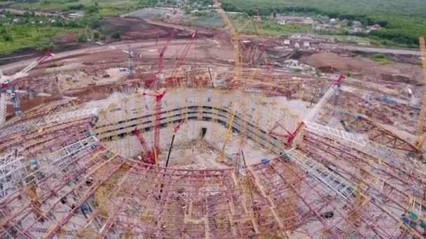flying drone is showing works inside stadium under construction, moving under building