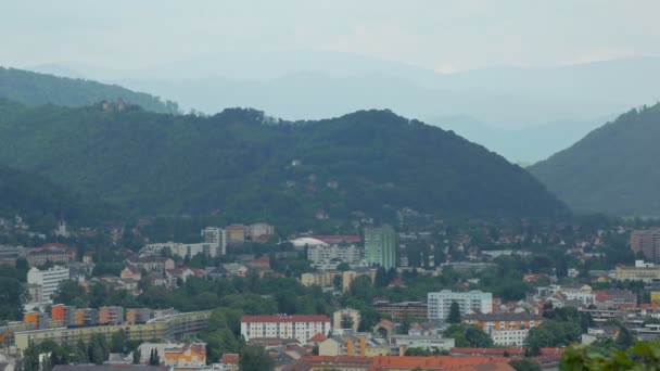beautiful mountain covered by dense forest near town area in spring day, calm cityscape