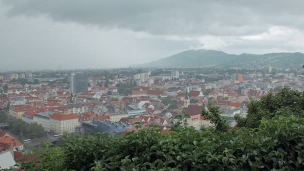 thunderclouds are moving slowly over Graz town and high mountains in spring day