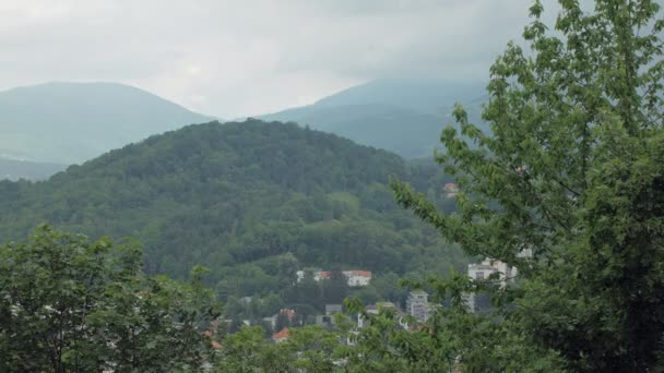view on picturesque hills near city and thunderclouds over it in spring day