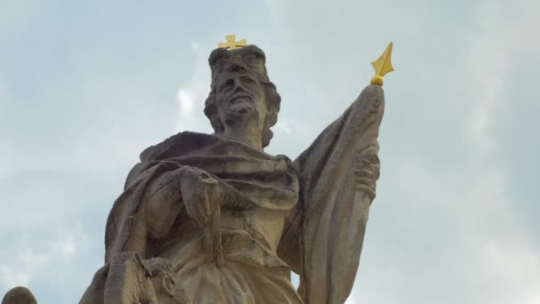 Kamenná středověká socha muže ve věku, který hledí proti obloze