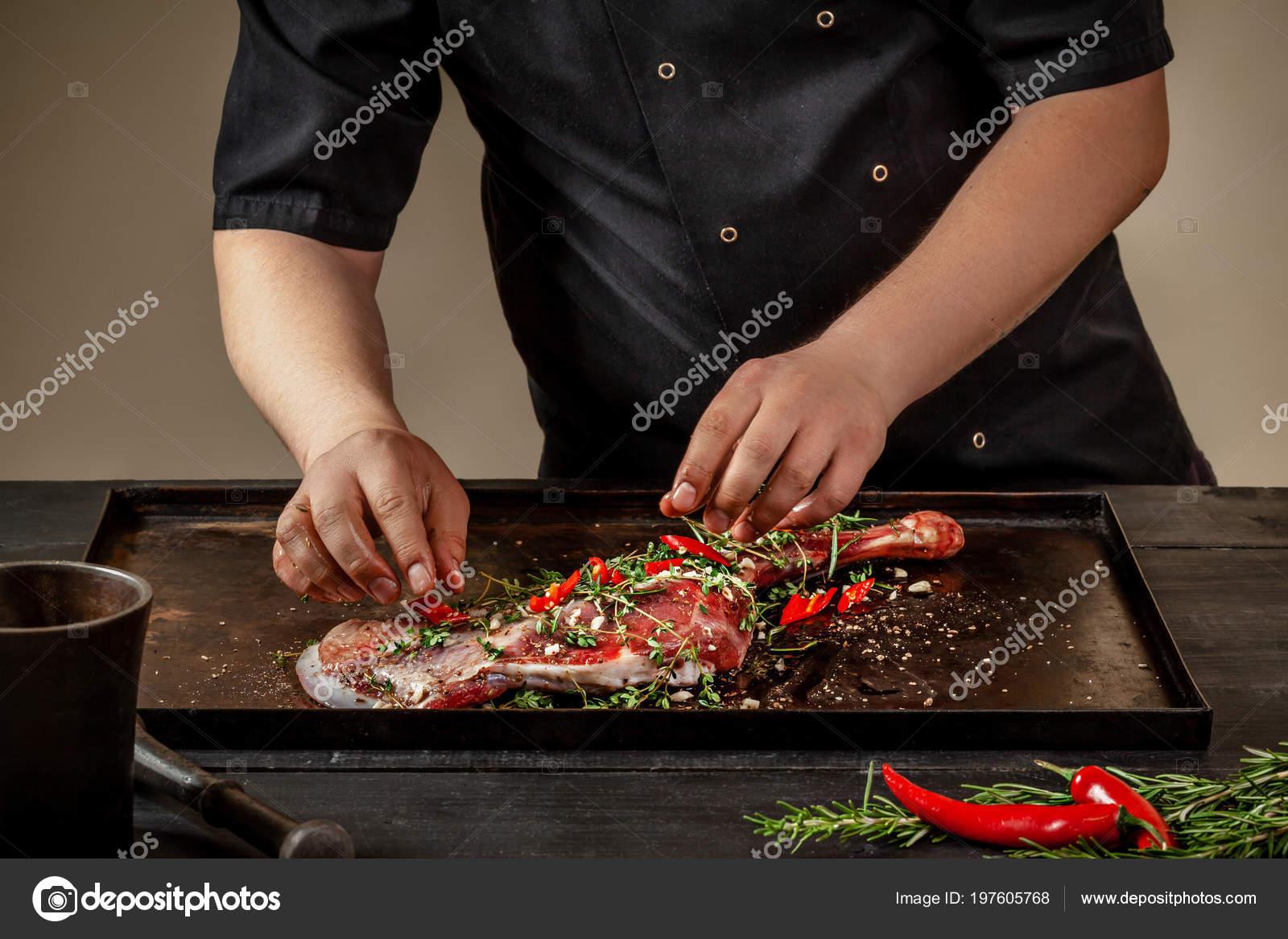 Αρσενικό σεφ τρίβοντας ωμά αρνιού με χόρτα και τα μπαχαρικά σε πέτρινο  δίσκο στο ξύλινο τραπέζι. Σεφ μαγειρικής ορεκτικές Κότσι αρνίσιο– εικόνα  αρχείου 9c99579aa1b
