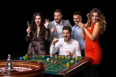 Group of young people looking excited at spinning roulette