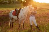 Jockey junge Mädchen streichelt und umarmt Schimmel im Abendsonnenuntergang. Sonneneruption