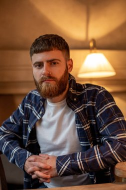 Portrait handsome bearded man wearing plaid shirt at modern cafe.