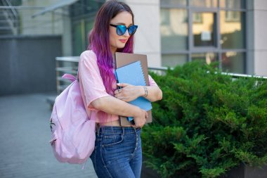 Portrait beautiful female writer dressed in casual outfit holding modern laptop in hand with backpack.