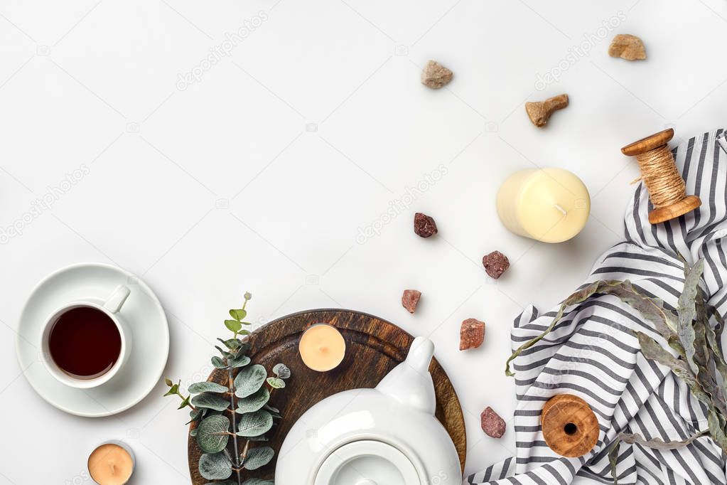 Still life with tea cup and the contents of a workspace composed. Different objects on white table. Flat lay