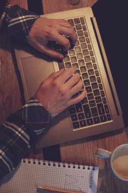 Young man drinking coffee in cafe and using laptop. Mans hands