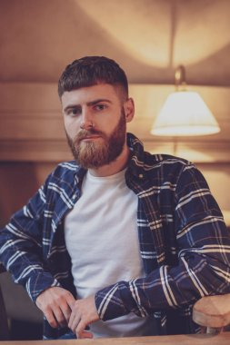 Portrait handsome bearded man wearing plaid shirt at modern cafe
