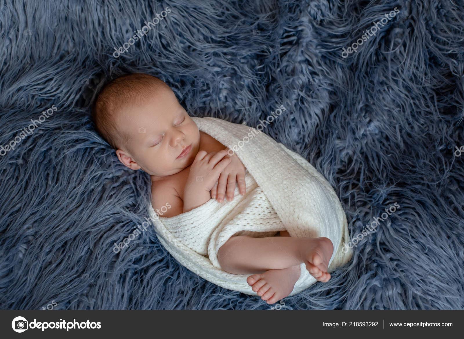 5b9f64407f54 Newborn baby boy in bed. New born child sleeping under a white ...
