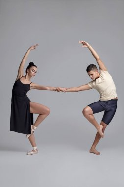 Two young ballet dancers are posing over a gray studio background. Attractive man in black shorts with beige t-shirt and beautiful woman in a black dress and white pointe shoes are dancing together stock vector