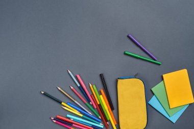 Flat lay photo of a workspace desk with school stationers, such as felt-tip pens, yellow pencil case, stickers and colored pencils. Mockup of learning process. Top view with copy space on gray stock vector