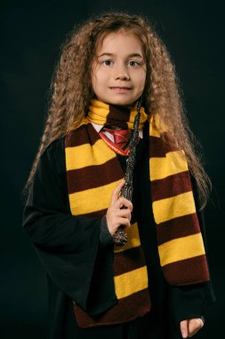 Portrait of a little witch girl with long brown hair dressed in dark coat, holding magic wand in her hand, posing on black studio background.