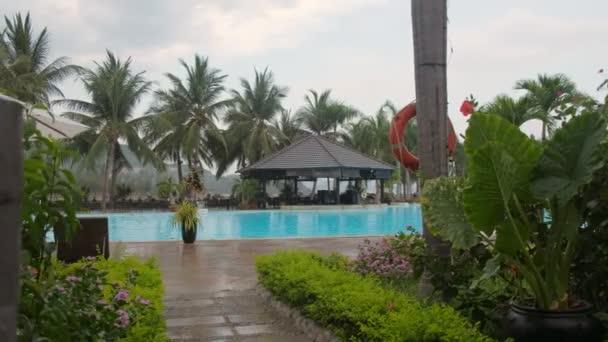 Déšť padá na lehátko u bazénu v luxusní hotel