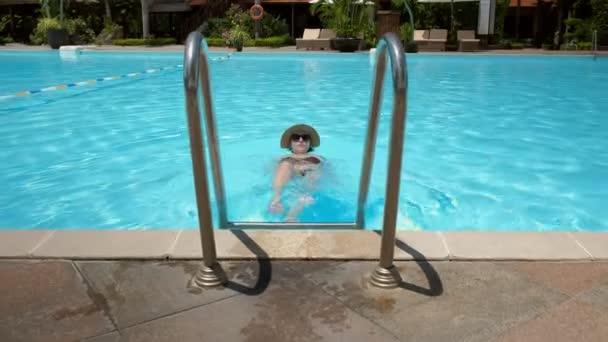 Žena, plovoucí a relaxaci v bazénu. plavat ven