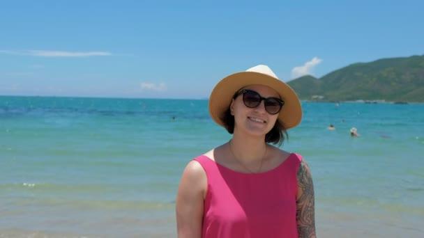 Gyönyörű fiatal barna nő visel egy fürdőruhát és a nap kalap, napszemüveg, állandó egy komp fedélzetén, élvezve a többi, szépsége, a tenger, boldog, mosolyog