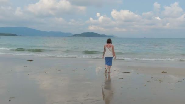 eine Rückansicht einer jungen tätowierten Frau geht am Meeresufer entlang mit einer wunderschönen Bucht im Hintergrund