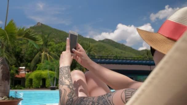 Egy fiatal tetovált nő egy kalap elfog a gyönyörű kilátást a medence mellett