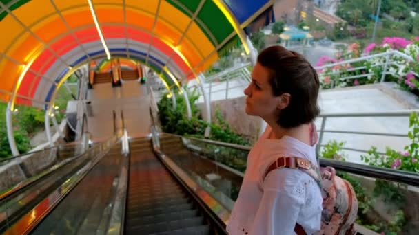 An aerial view of a beautiful young woman going down by the colorful escalator in an amusement park