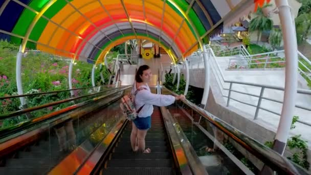 An aerial view of a pretty young woman going down by the colorful escalator in an entertainment park