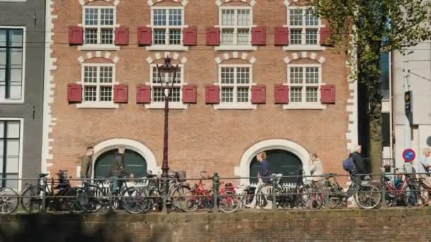 Amesterdam, Netherlands, May 2018: Beautiful Amsterdam street. Pedestrians walk along the canal, bicycles ride. Against the background of typical brick houses. City life