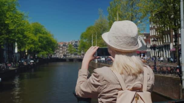Ženské turista v klobouku a s batohem obrázky, nádherný výhled na kanál v Amsterdamu. Turistika v Nizozemsku a Evropa konceptu