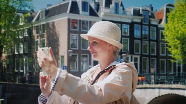 A woman tourist takes pictures of herself in a picturesque place near the canal. Tourism in the Netherlands and Amsterdam