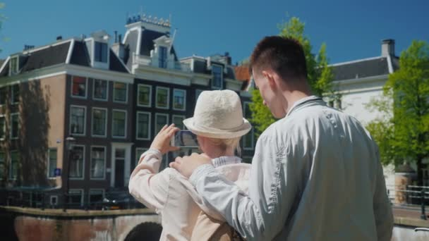 Mom with an adult son takes a beautiful view of the canal in Amsterdam. Family holiday in Europe concept