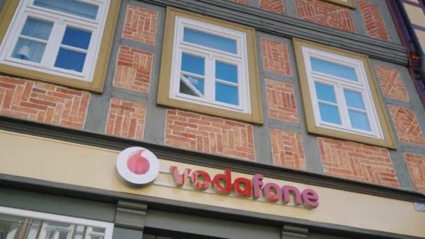 Wernigerode, Německo, květen 2018: Znamení Vodafone je jedním z největších mobilních operátorů v Evropě. Na fasádě starého německého domu s rozpoznatelný styl stavby